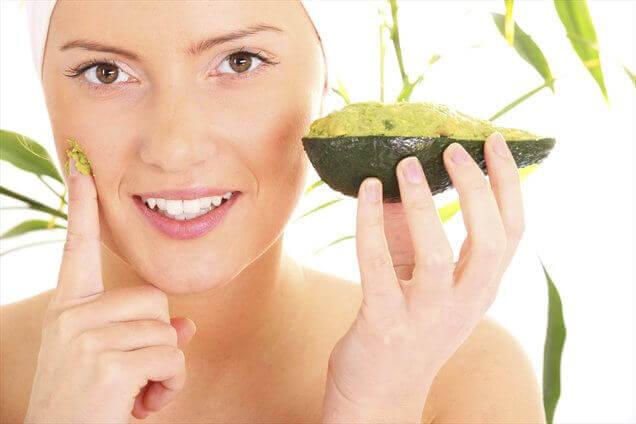vrouw smeert masker met avocado op