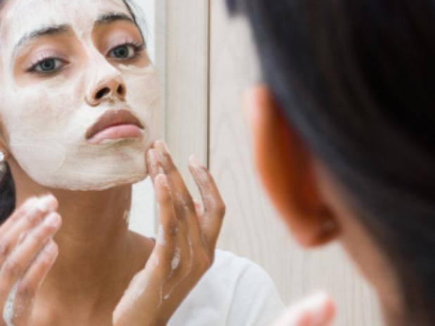 vrouw smeert creme op haar gezicht