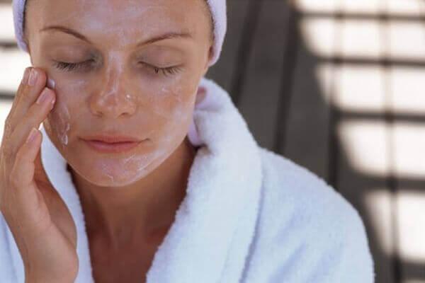 vrouw smeert masker op haar gezicht