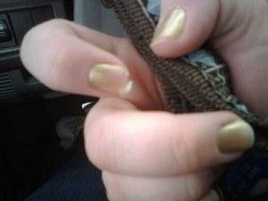 Meisje met goud gelakte schilferende nagels