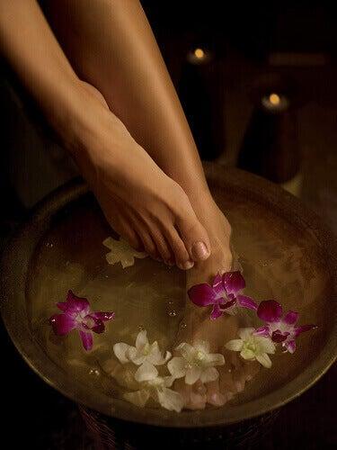 Voeten in bad met bloemblaadjes