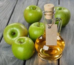 Fles appelazijn met appels op tafel