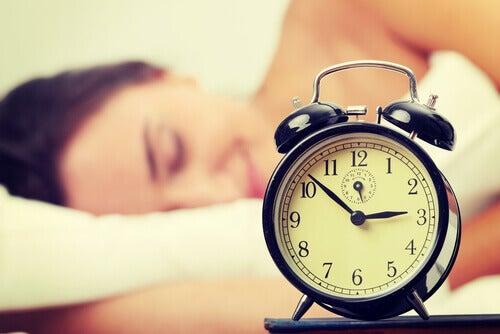 Wekker met slapende vrouw op de achtergrond