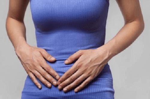 Vrouw met handen op de buik tegen maagkramp