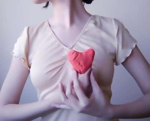 Vrouw houdt hart van klei voor borst