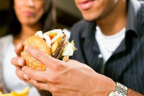 Een man eet een hamburger