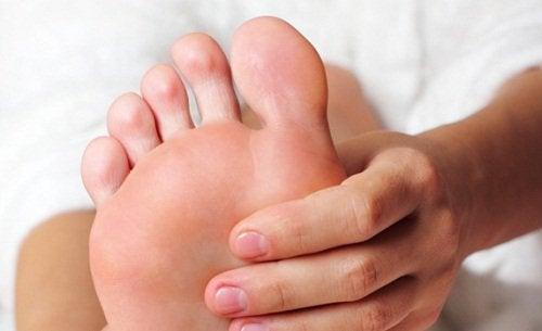 Vrouw geeft zichzelf een voetmassage