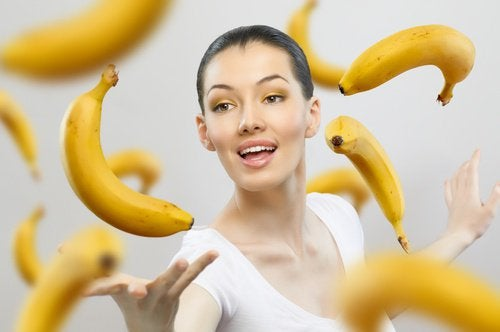 Vrouw met rijpe bananen om zich heen