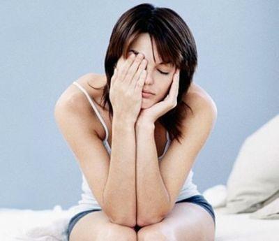 Vermoeide vrouw zit op rand van haar bed