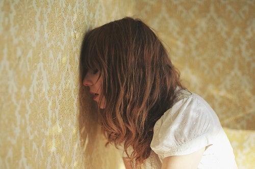 Vrouw leunt met hoofd tegen de muur