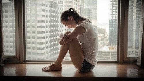 verdrietige vrouw bij een raam