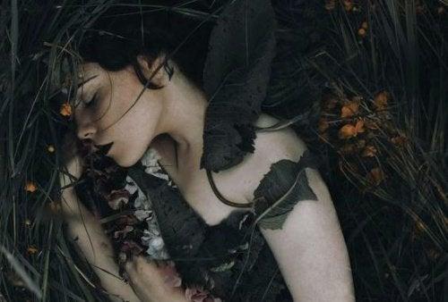 vrouw ligt tussen bladeren