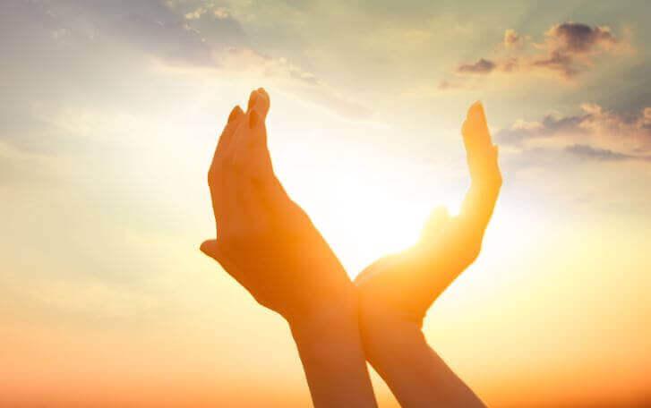 handen bij ondergaande zon