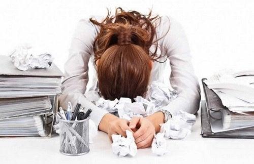 Overwerkte vrouw leunt op bureau