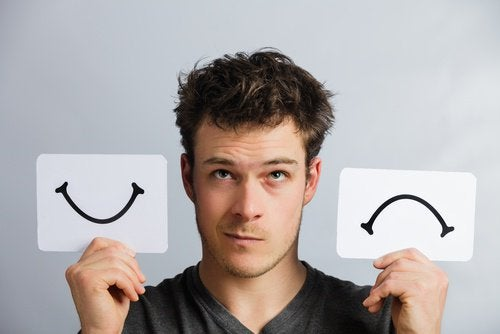 Man die een lachend en een fronsend mondje vast heeft