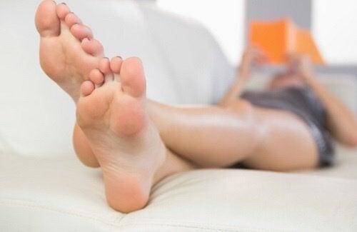 Vrouw met blote voeten ligt te lezen