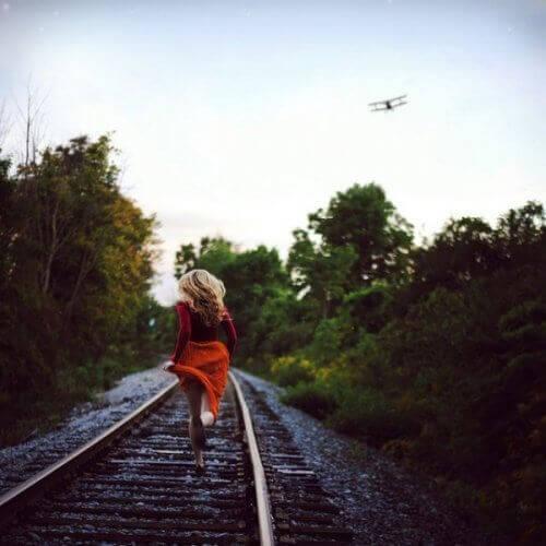 Vrouw die over spoor rent