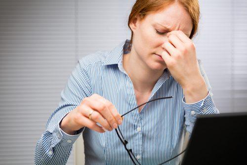 Werkende vrouw die last heeft van hoofdpijn