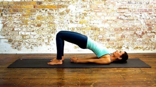 Yogahoudingen voor een platte buik de brughouding