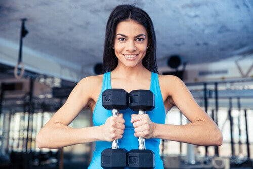 Vrouw Die Met Gewichten In Haar Handen In De Sportschool Staat