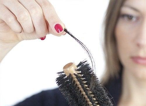 Vrouw Die Een Pluk Haar Uit Haar Borstel Haalt Omdat Ze Last Heeft Van Haaruitval Als Een Van De Symptomen Van Stress