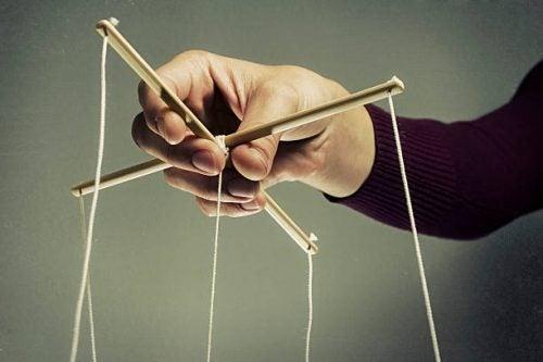 Hand Dat De Touwtjes Van Een Marionet Bestuurt