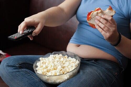 Meisje Dat Op De Bank Tv Zit Te Kijken Met Een Bak Popcorn Op Schoot En Een Broodje In Haar Hand Als Voorbeeld Van Slechte Afvalgewoontes