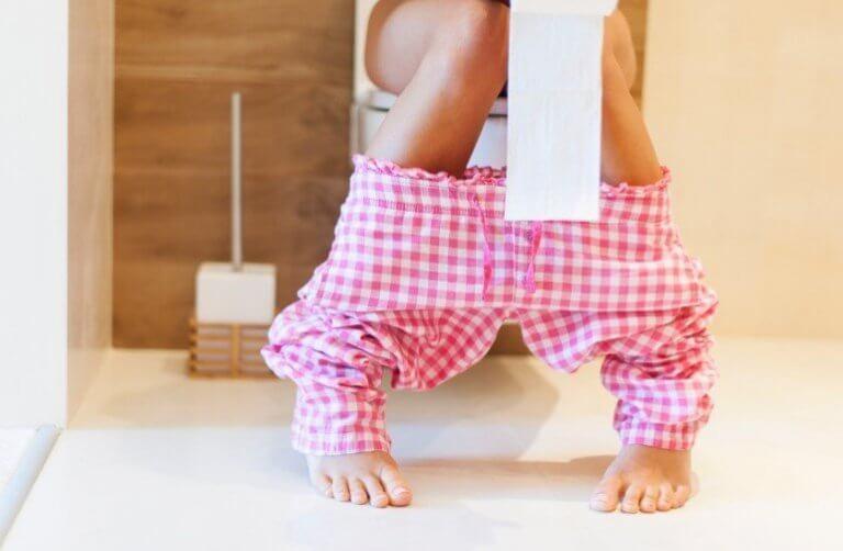 Vrouw met roze geruite broek op het toilet