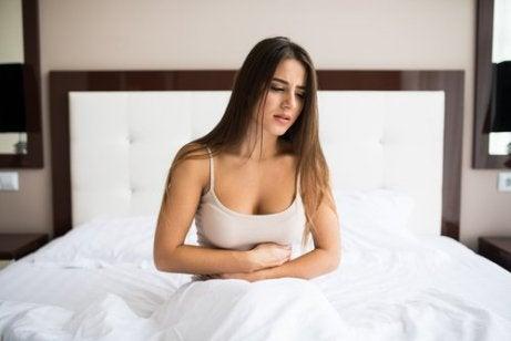 Vrouw op bed met armen om de buik geslagen