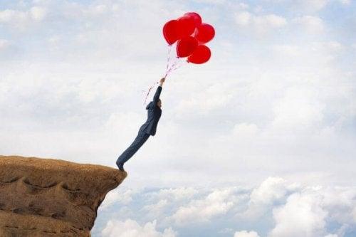 Man met ballonnen die van een rots springt