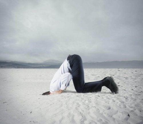 Man die zijn kop in het zand steekt om onopgeloste dingen te vermijden