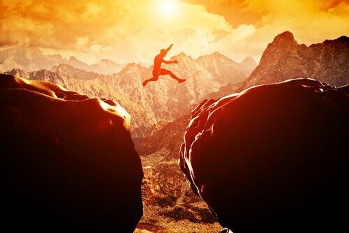Man die van de ene rots naar de andere springt