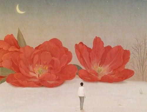 Man die voor twee grote rode bloemen staat