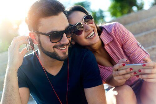 Lachende man en vrouw die muziek luisteren