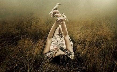 Vrouw die ontspannen in het gras ligt met twee vogels
