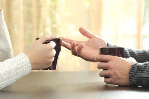 Twee mensen die onder het genot van een kop koffie met elkaar praten