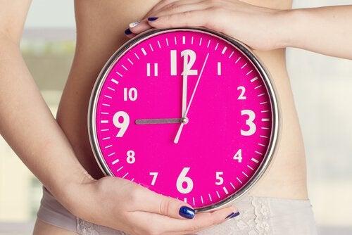 Meisje dat een klok voor haar buik houdt