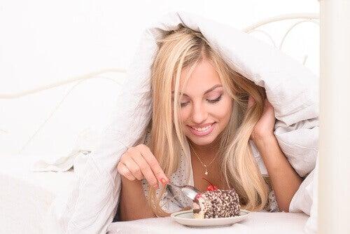 Meisje dat in bed een ongezonde snack eet