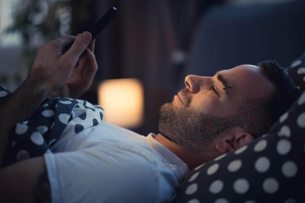 Man met smartphone in bed lijdt aan nomofobie