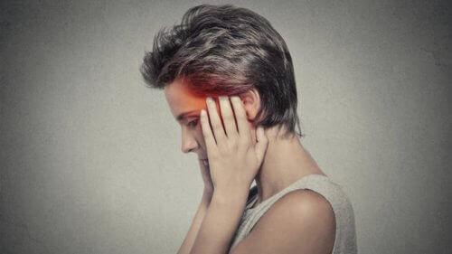 Vrouw die haar handen tegen haar slapen houdt omdat ze last heeft van nachtelijke hoofdpijn
