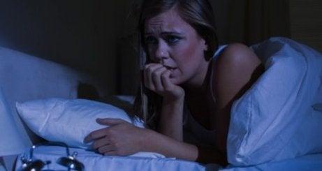 Vrouw die 's nachts wakker is omdat ze last heeft van nachtelijke paniekaanvallen