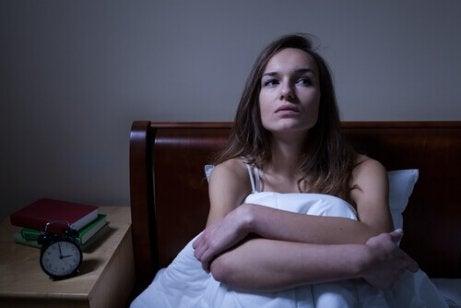 Vrouw die rechtop in bed zit omdat ze last heeft van nachtelijke paniekaanvallen