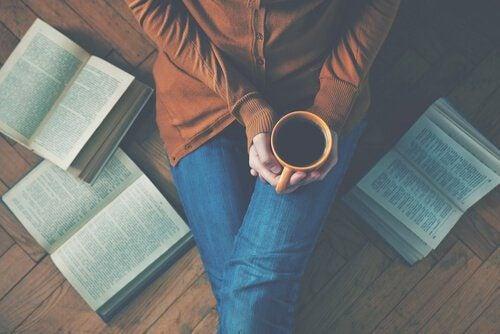 Vrouw met kop koffie en boeken