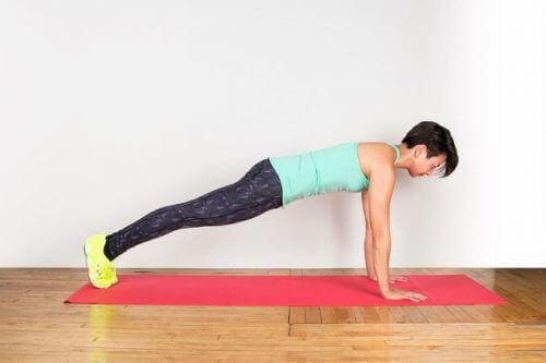 Vrouw doet de plank op yogamat