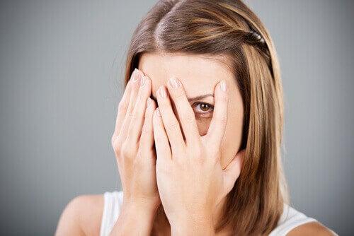 Vrouw die haar handen voor haar gezicht houdt