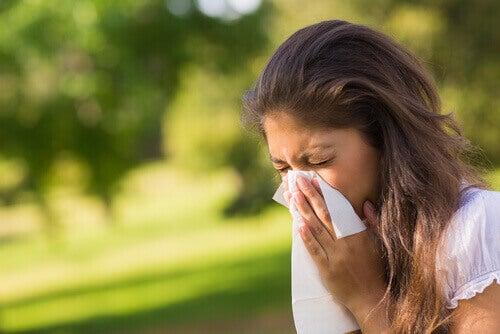 Vrouw die haar neus snuit omdat ze last heeft van de symptomen van sinusitis