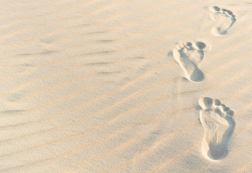 Niet bang zijn om alleen te zijn voetstappen in het zand