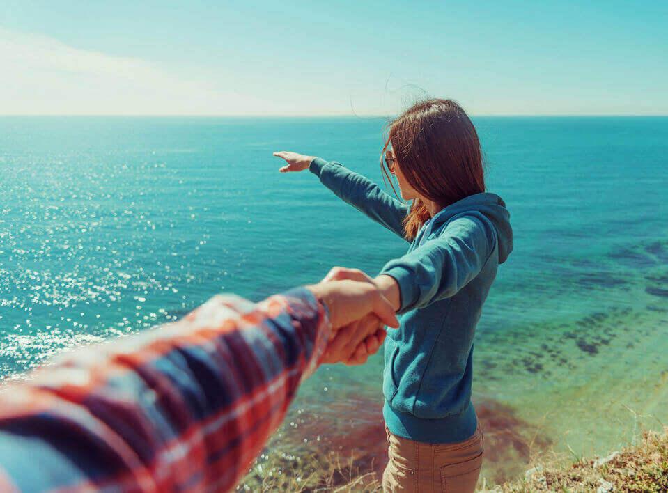 Vrouw die naar de horizon wijst, want je kunt mannen aantrekken door hun interesse te wekken