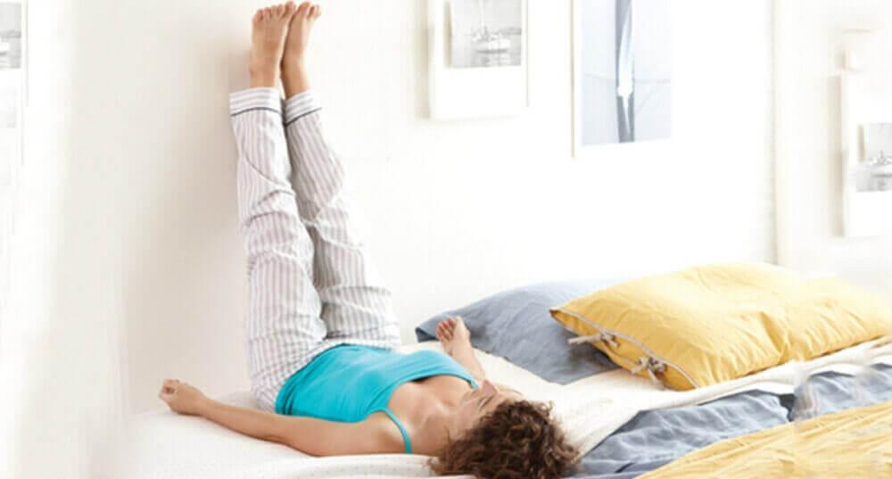 Vrouw die haar benen omhoog houdt tegen de muur