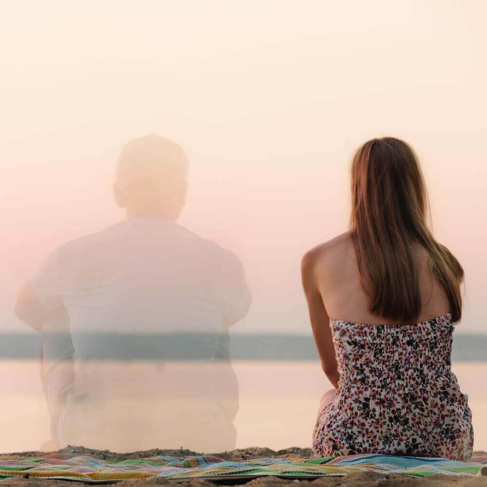 Vrouw die alleen zit op het strand met de gedachte van haar ex naast zich